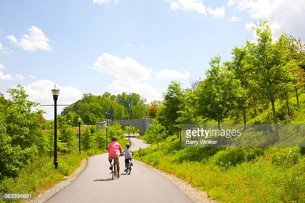 man and boy bicycling on path in atlanta park - piedmont park atlanta georgia stock pictures, royalty-free photos & images