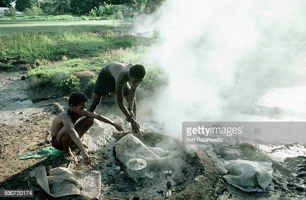 Man and Boy Cook over Natural Hot Spring