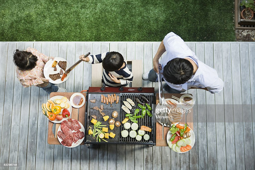 Man and boy cooking barbecue for family : Stock Photo