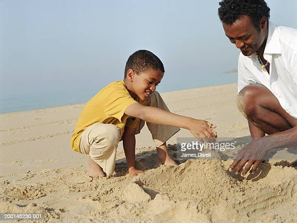 Man and boy (7-9) crouching on beach, building sand castle