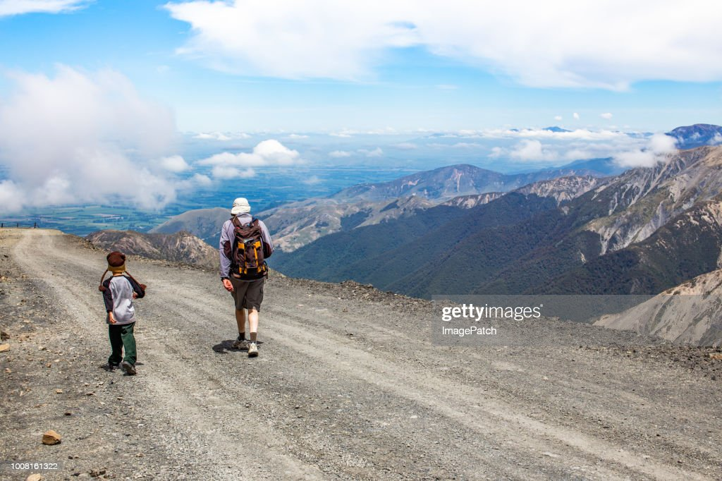 man and boy exploring the outdoors on a mountain road above the