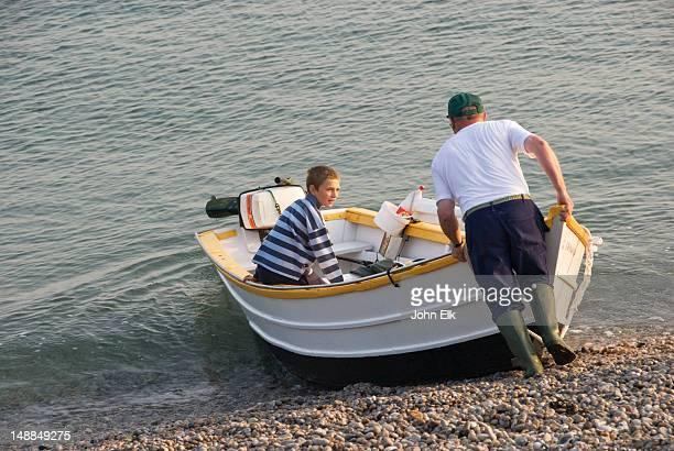 Man and boy launching boat.
