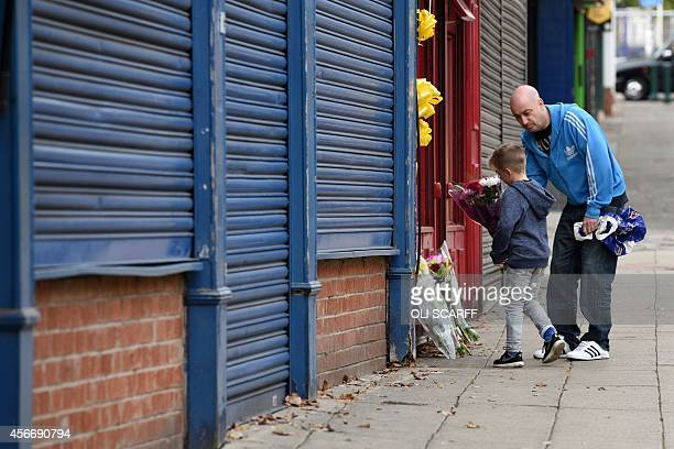 A man and boy lay a floral tribute outside the office minicab office where murdered aid worker Alan Henning worked in Eccles north west England on...