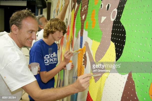 A man and boy painting a mural in the hallway in Citrus Grove Middle School at Hands on Miami Day