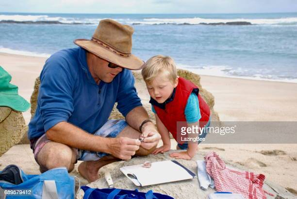 Man and Boy prepare bait for Surf Fishing in Summer