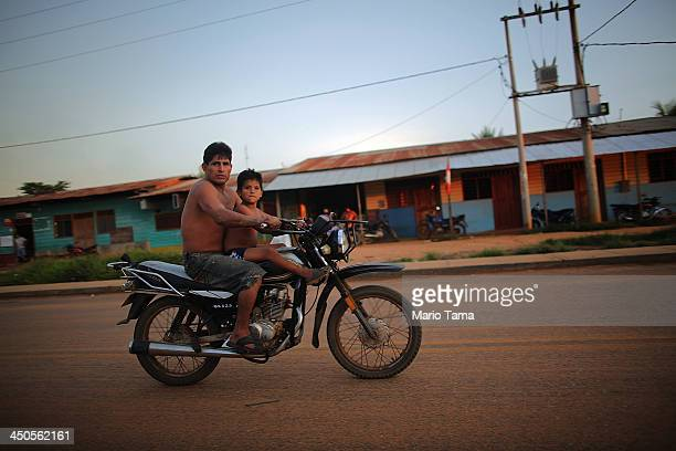 A man and boy ride a motorcycle in a deforested section along the Interoceanic Highway in the Amazon lowlands on November 16 2013 in Madre de Dios...