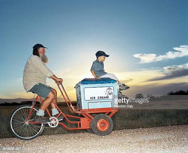 Man and boy (5-7) riding mobile ice cream cart, profile
