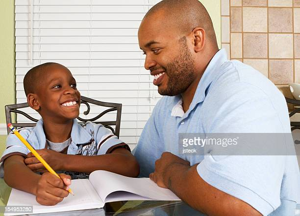 Man and boy seated at table with pencil and notebook smiling
