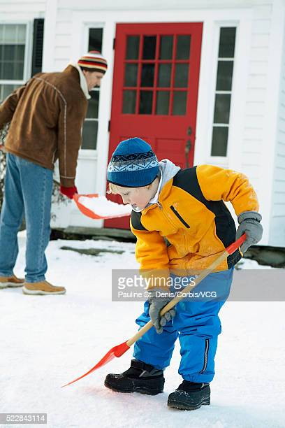 Man and boy shoveling snow