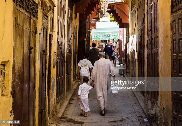 Man and boy walk thorough the Fez medina, Morocco
