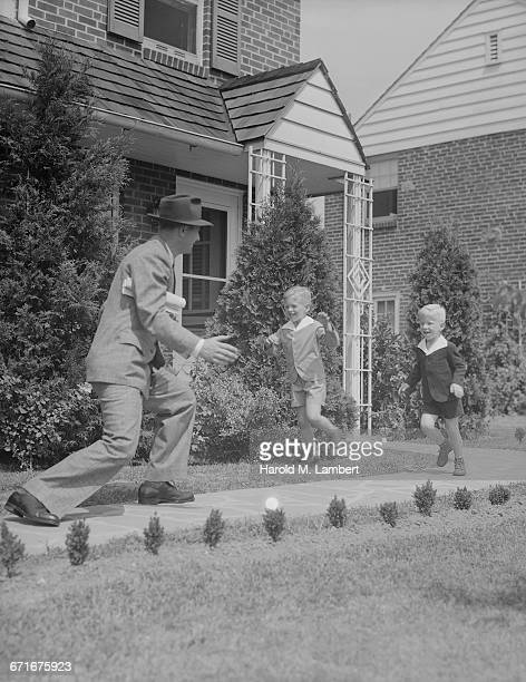 man and boys running in front of house - {{relatedsearchurl(carousel.phrase)}} fotografías e imágenes de stock