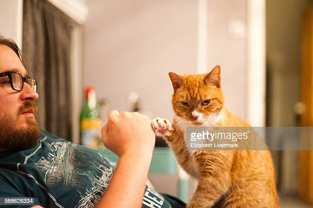 Man and cat do a fist bump