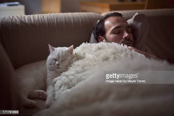 Man and cat having a nap on sofa