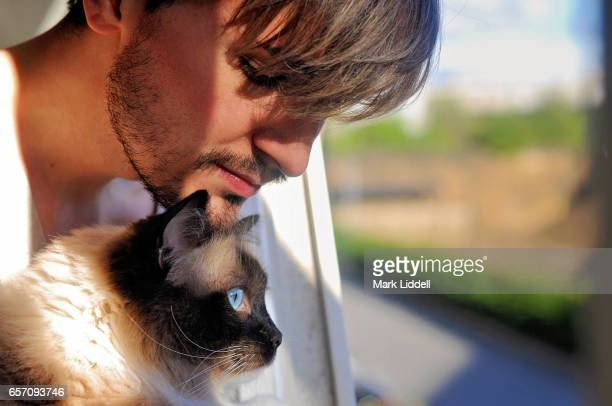 Man and cat looking out of window