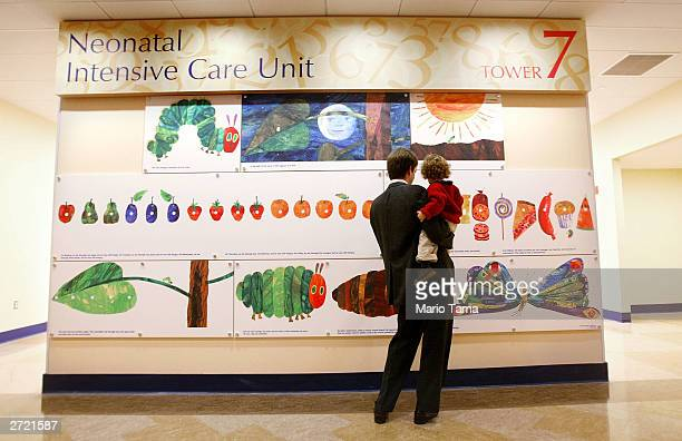 A man and child look at a decorative mural at the entrance to the neonatal intensive care unit during the grand opening of the Morgan Stanley...