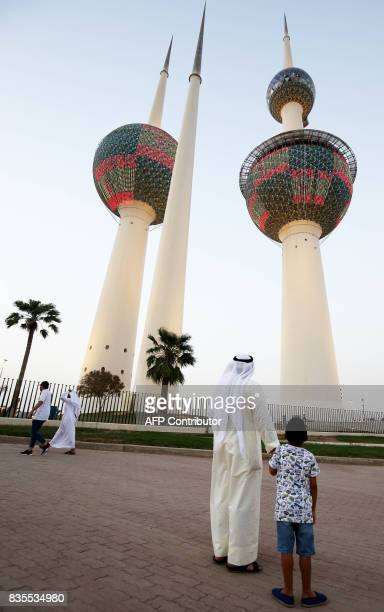 A man and child look up at Kuwait's Towers in Kuwait City illuminated in the colours of the Spanish flag on August 19 in tribute to the victims of...