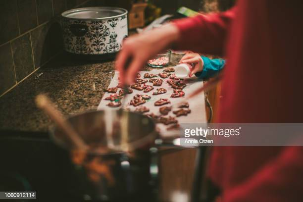 man and child make christmas treats together - annie sprinkle stock pictures, royalty-free photos & images