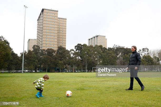 Man and child play with a soccer ball near the block of public housing towers in Kensington on July 07, 2020 in Melbourne, Australia. Nine public...