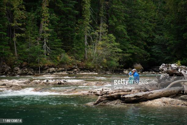 man and child sitting on log fishing in a river in washington state - wide shot stock pictures, royalty-free photos & images
