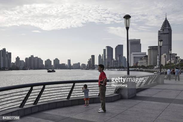 A man and child standing on the bund look across the Huangpu River in Shanghai China on Monday Sept 4 2017 The Chinese central bank's tight leash on...