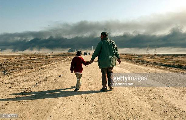 Man and child walk on a road near the entrance of the besieged city of Basra as oil fires burn in the distance March 29, 2003 in Iraq. Baath Party...