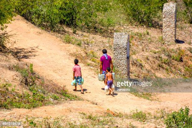 Man and children carrying water in the sertao of Brazil