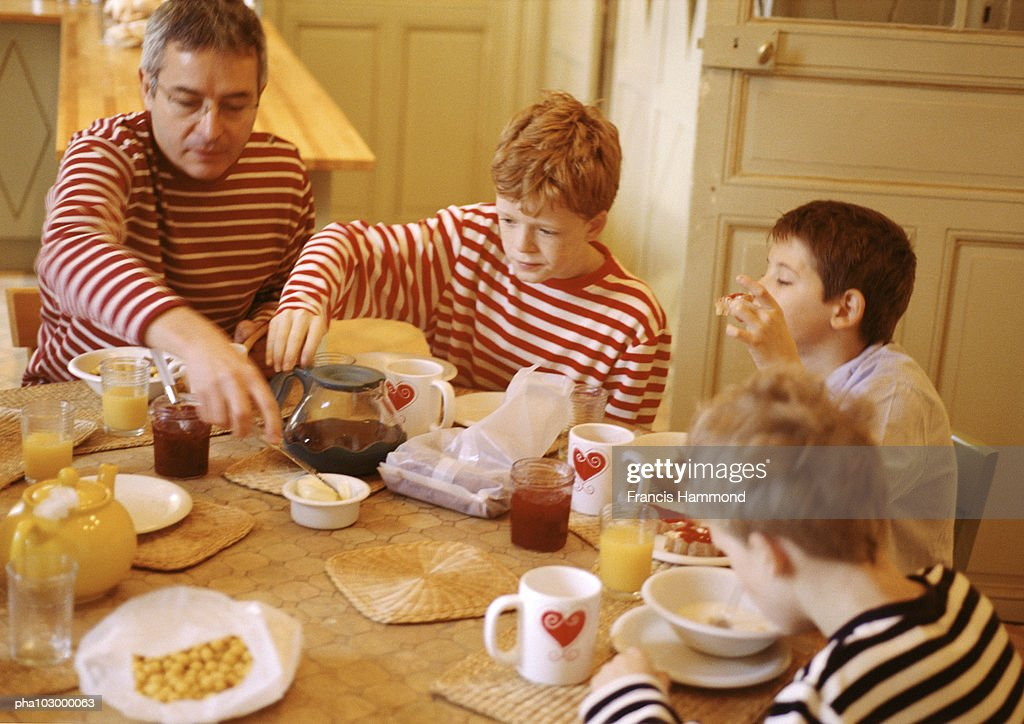 Man and children having breakfast : Stockfoto