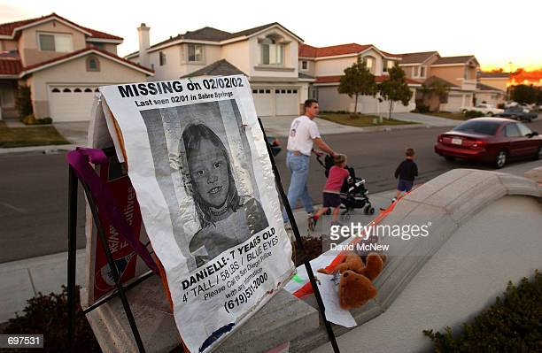 A man and children walk past a poster for missing sevenyearold Danielle van Dam at a park on the van Dams suburban street February 13 in the commuity...