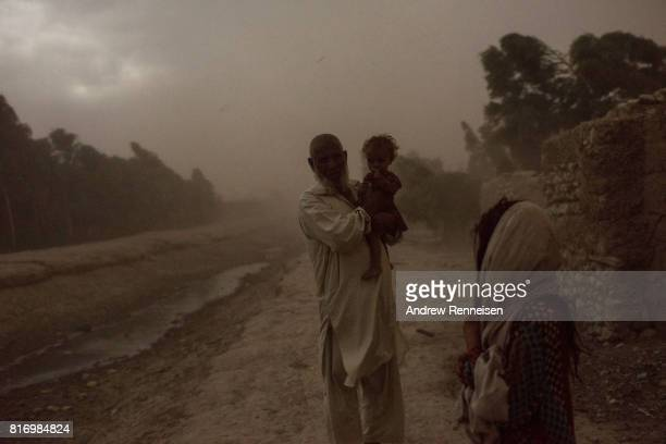 A man and children who were displaced by Islamic State of Iraq and Syria Khorasan stand outside their current home during a storm on July 14 in Surkh...