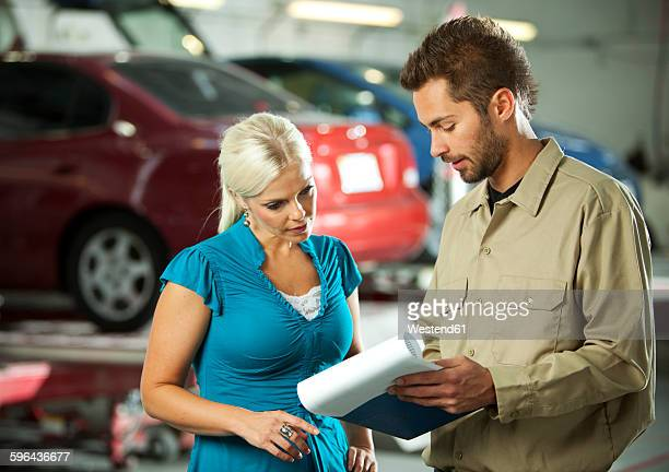 Man and customer in repair garage discussing ckeck list