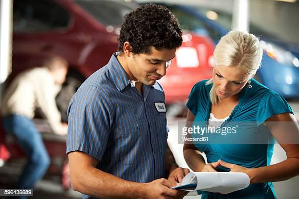 Man and customer in repair garage looking at ckeck list