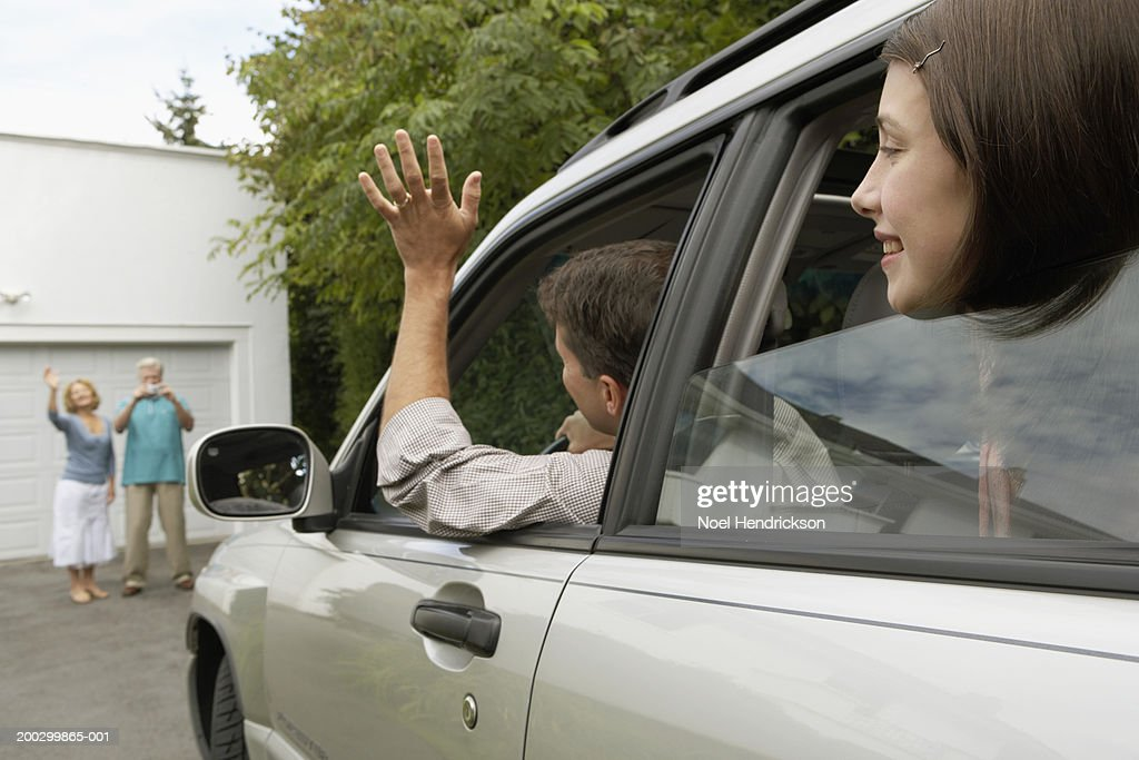 Man and daughter (13-15 years) in car waving to senior couple on drive : Stock Photo