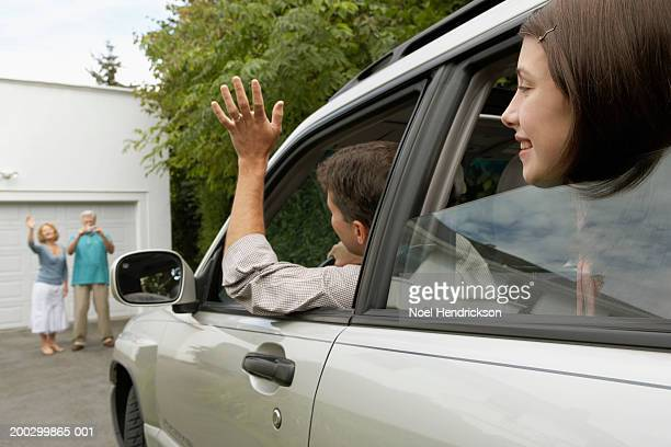 man and daughter (13-15 years) in car waving to senior couple on drive - visit stock pictures, royalty-free photos & images