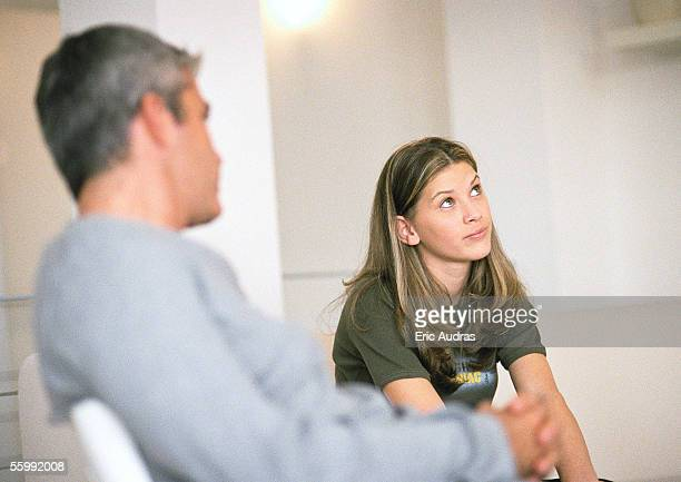 Man and daughter sitting, man looking at daughter