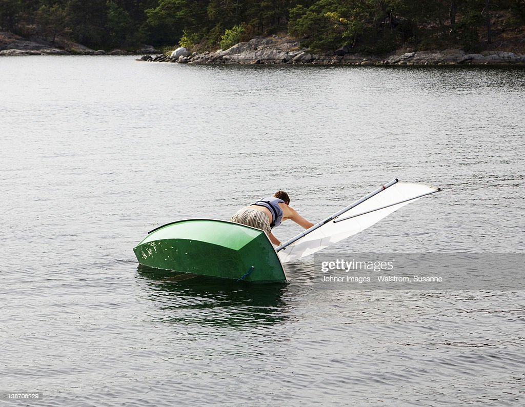 Man and dinghy falling into water : Stock Photo