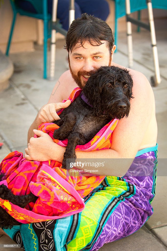 man and dog after swimming in a pool : Stock Photo