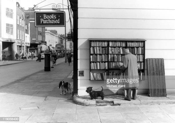 A man and dog at a secondhand book shopin King's Road Chelsea London England Britain 1959