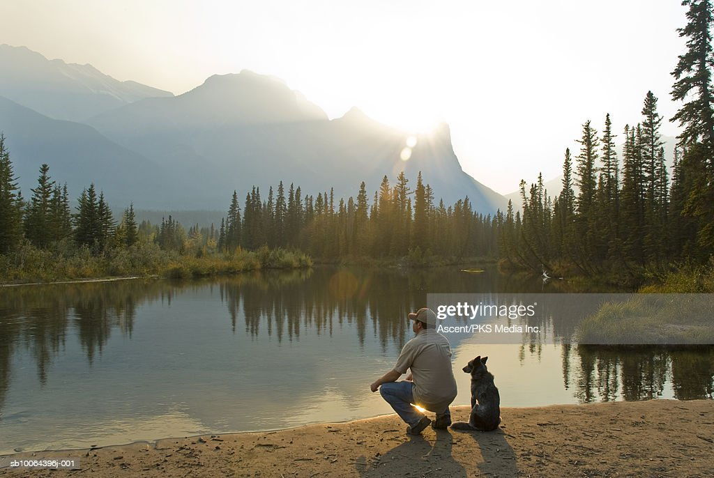 Man and dog beside lake in mountains, rear view : Stock Photo