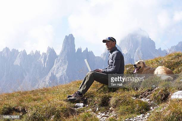 man and dog in mountains with laptop - 岩壁 ストックフォトと画像