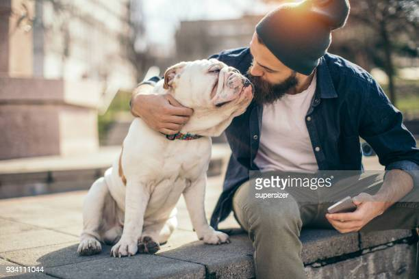 man and dog in the park - english bulldog stock pictures, royalty-free photos & images