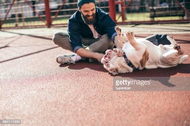 hombre y el perro en el parque - mid adult men fotografías e imágenes de stock