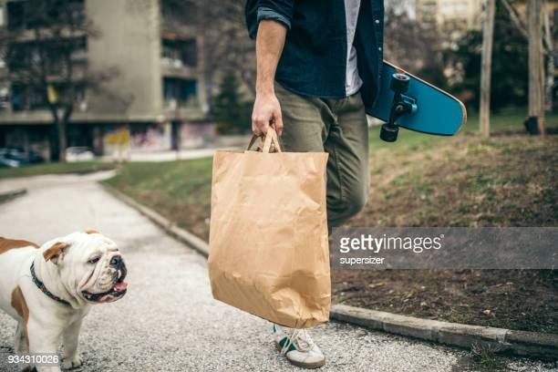 man and dog in the park - grocery bag stock pictures, royalty-free photos & images