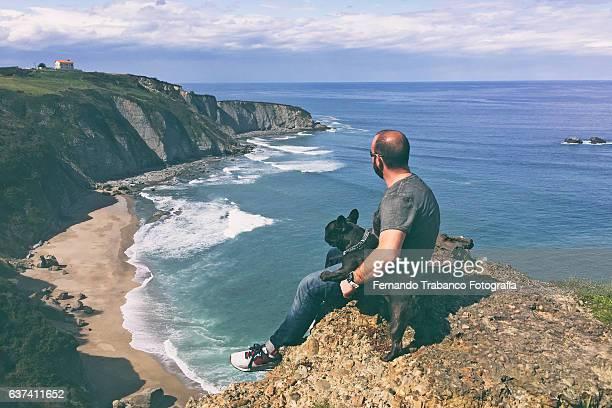 Man and dog looking at sea and beach