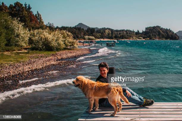 man and dog on a dock at the lake - patagonia argentina - bariloche stock pictures, royalty-free photos & images
