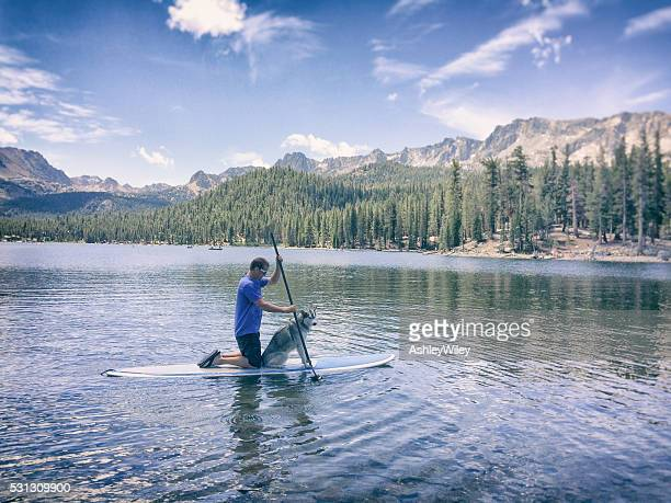 Man and dog paddle on a lake in Mammoth, California