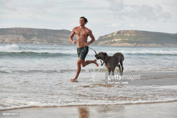 man and dog running on beach - matthew hale stock pictures, royalty-free photos & images