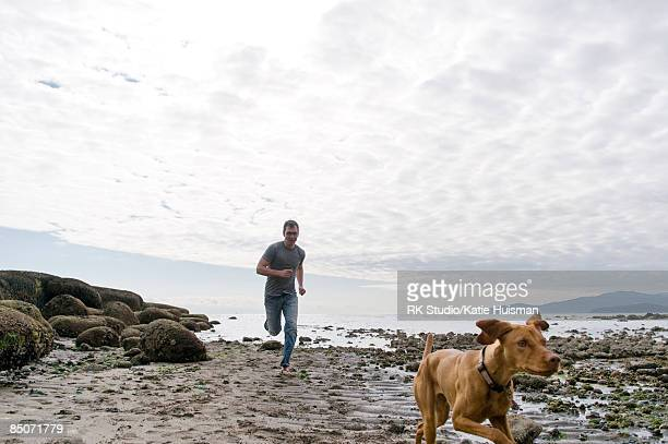 Man and dog running on rocky beach.