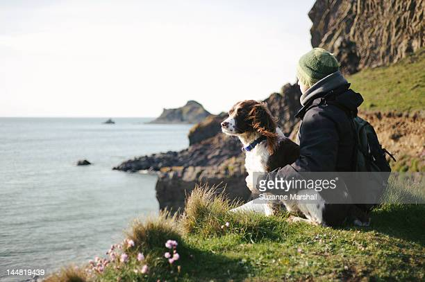 Man and dog siting on cliff looking out to sea