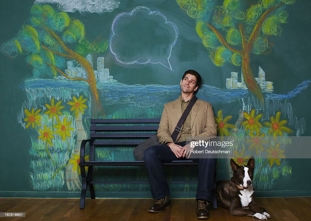 A man and dog sitting on a park bench thinking. : Stock Photo