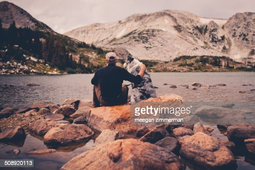 Man and dog sitting on rocks in water